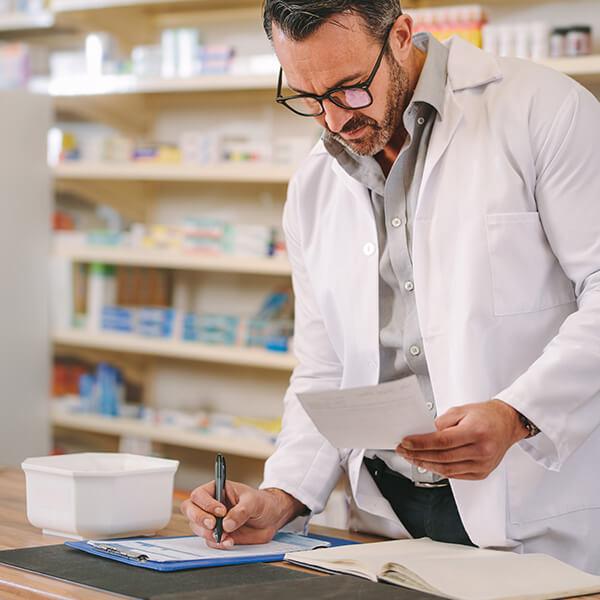 Ein Apotheker liest einen Zettel und macht sich auf einem anderen Zettel Notizen.