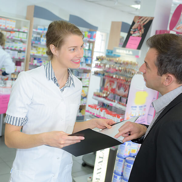 Ein Mann im Anzug erklärt einer Apothekerin etwas und zeigt dabei auf Unterlagen.