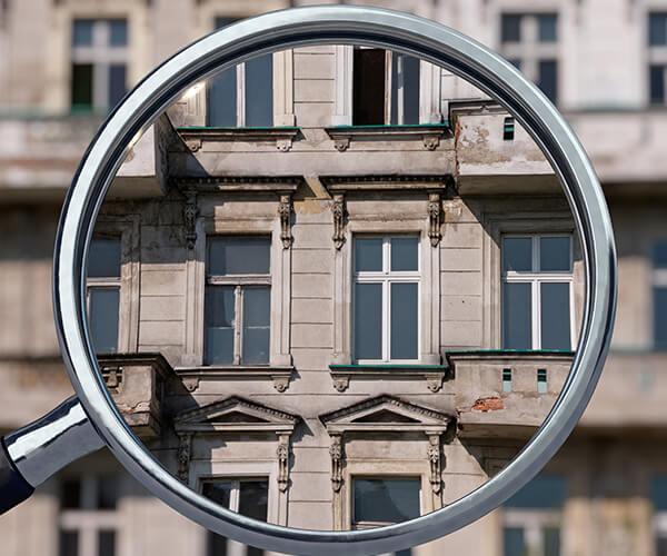 Durch eine Lupe sieht man den Teil eines Hauses vergrößert.